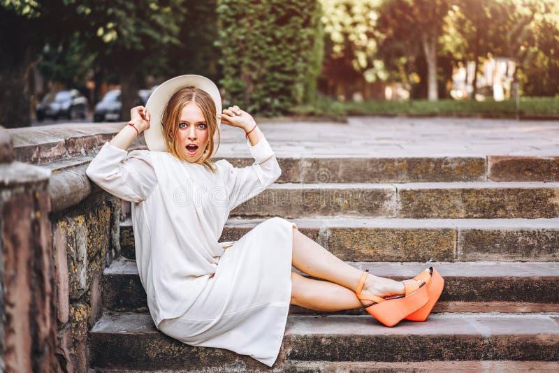 Donna abbastanza emozionante in vestito avvantaggioso bianco all'aperto fotografia stock