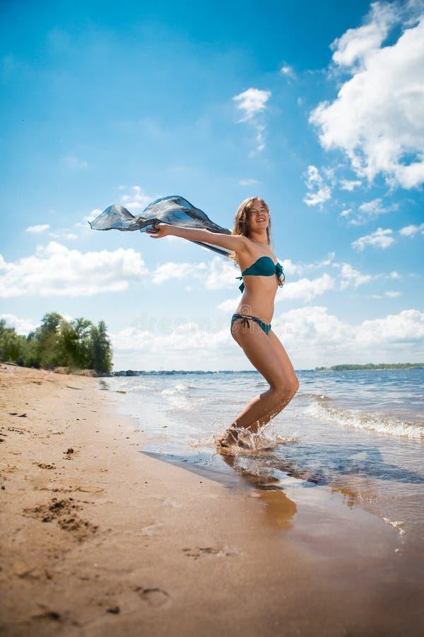 Donna abbastanza esile con il pareo nero che posa sulla spiaggia fotografia stock