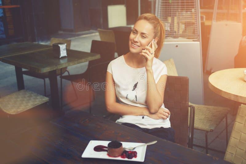 Donna abbastanza felice che chiama con lo Smart Phone durante la prima colazione di mattina in caffè fotografia stock