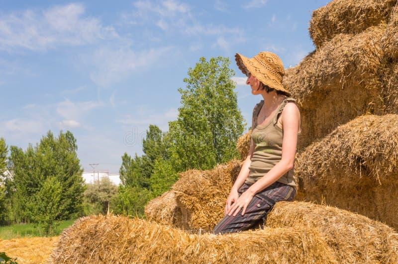 Donna abbastanza felice con il cappello che si siede sulle balle della paglia e che ottiene un certo resto fotografia stock libera da diritti