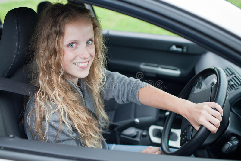 Donna abbastanza giovane che conduce la sua automobile fotografia stock libera da diritti