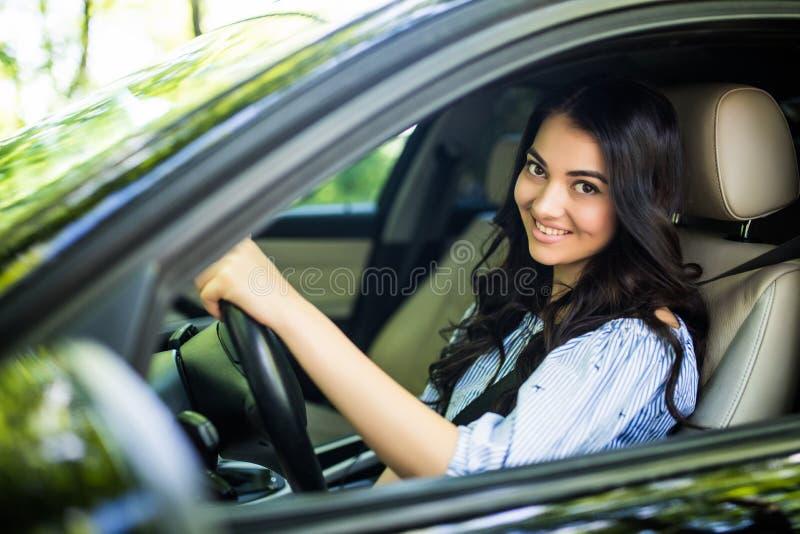 Donna abbastanza giovane che conduce la sua nuova automobile fotografia stock