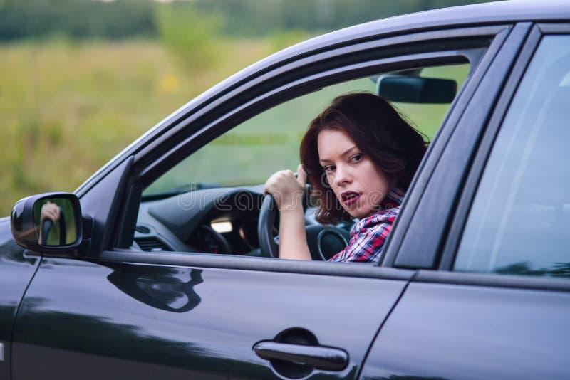 Donna abbastanza giovane che conduce la sua nuova automobile immagini stock libere da diritti