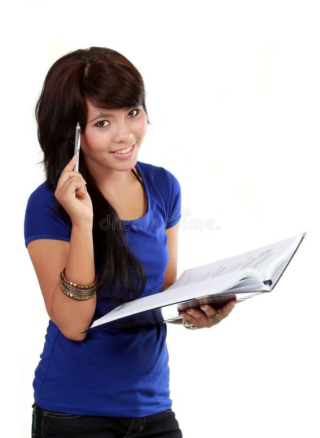 Donna abbastanza giovane che pensa, penna di holding fotografia stock libera da diritti