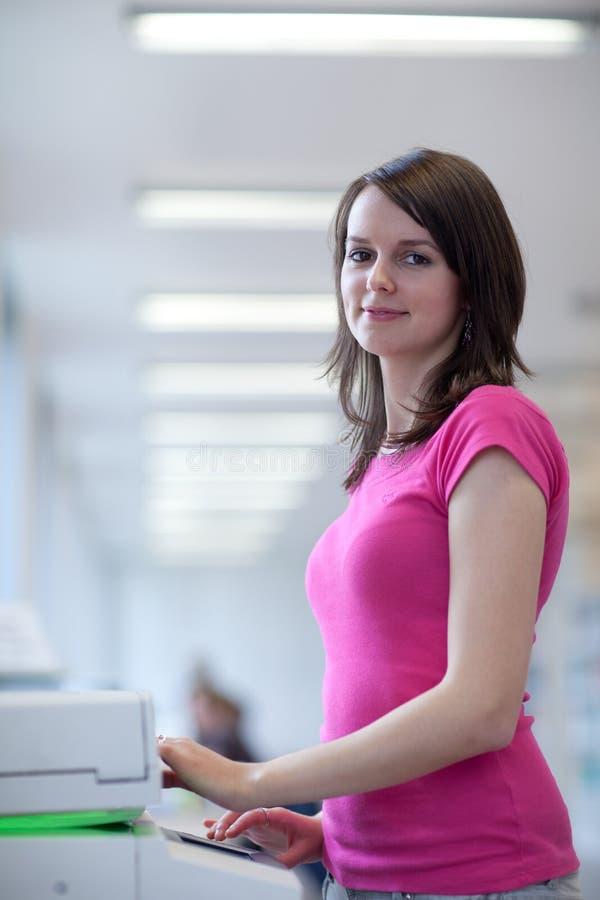 Donna abbastanza giovane che per mezzo di una macchina della copia fotografia stock libera da diritti