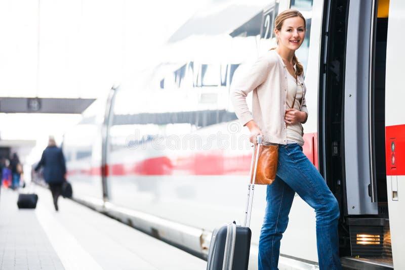 Donna abbastanza giovane che si imbarca su un treno immagine stock