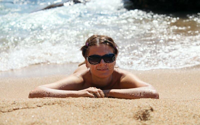 Donna abbastanza giovane che si trova giù sulla spiaggia sabbiosa fotografia stock libera da diritti