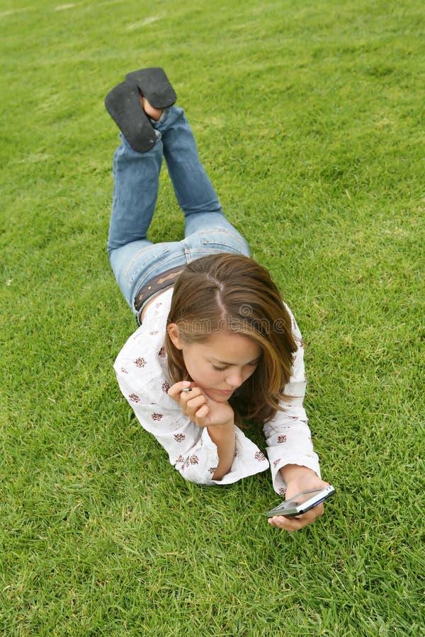 Donna abbastanza giovane che usando un PDA immagine stock
