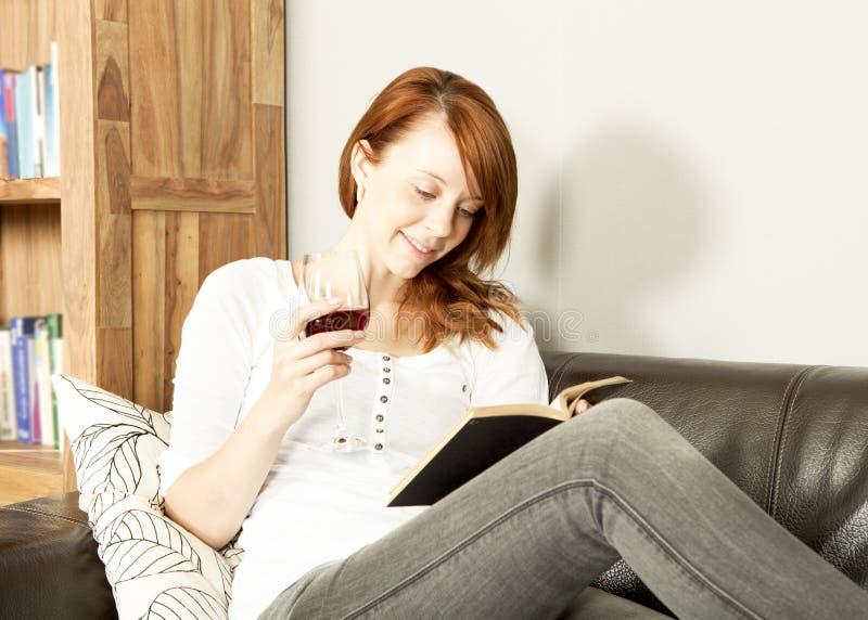 Donna abbastanza giovane della testarossa che legge un libro fotografia stock libera da diritti