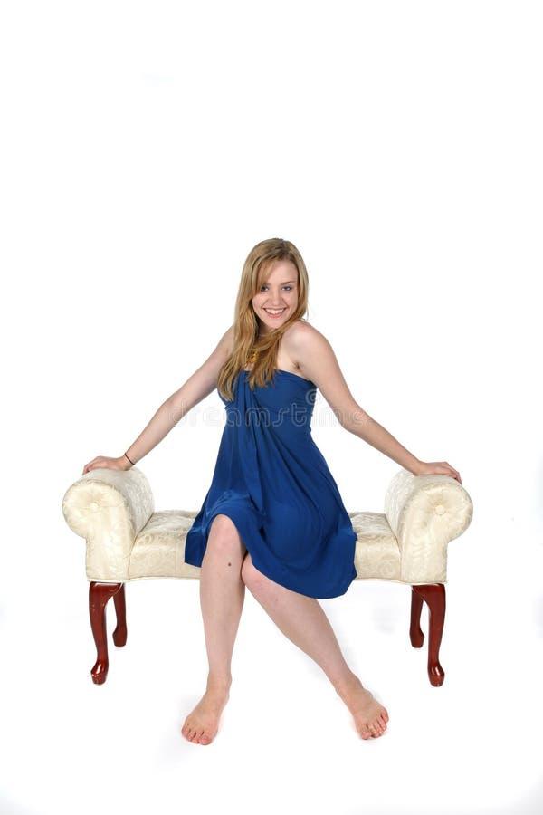 Donna abbastanza giovane in vestito blu che si siede sul banco immagine stock