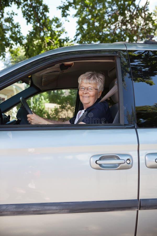 Donna abbastanza maggiore che conduce automobile fotografia stock
