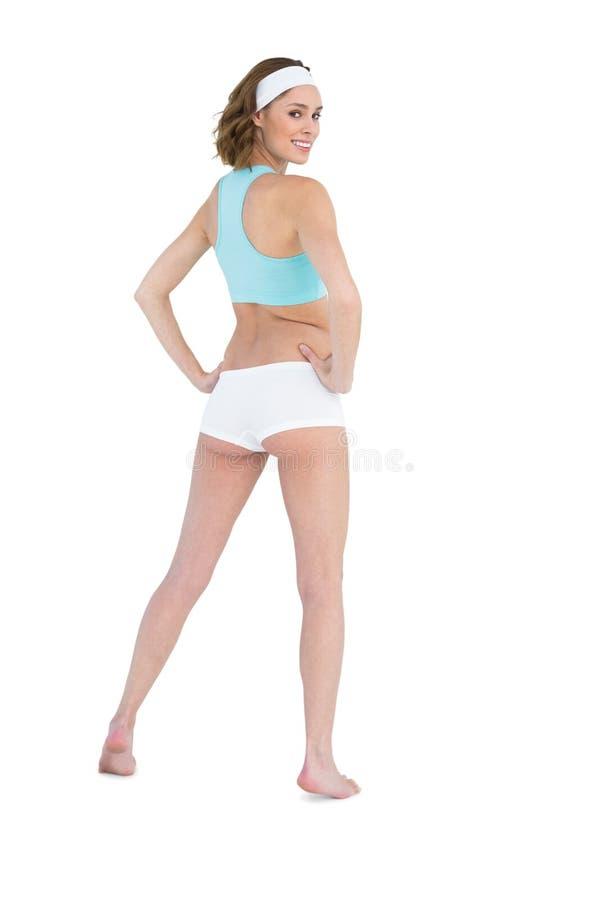 Donna abbastanza snella che esamina la sua spalla agli abiti sportivi d'uso della macchina fotografica immagine stock libera da diritti