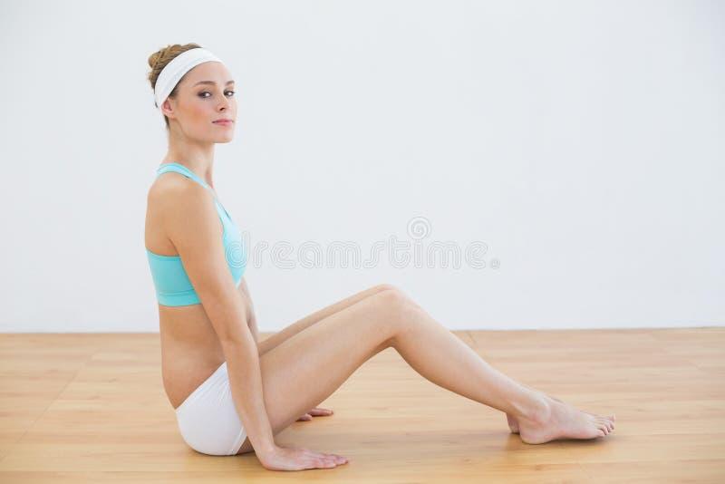 Donna abbastanza snella che si siede sul pavimento in abiti sportivi immagini stock libere da diritti