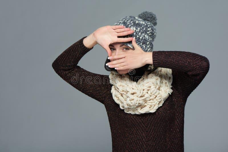 Donna in abbigliamento di inverno che fa una struttura con le sue mani immagine stock libera da diritti