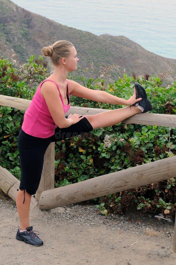 Donna in abiti sportivi all'aperto che allungano le sue gambe prima dell'correre fotografia stock libera da diritti