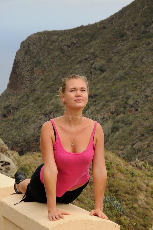 Donna in abiti sportivi all'aperto che allungano le sue gambe prima dell'correre fotografia stock