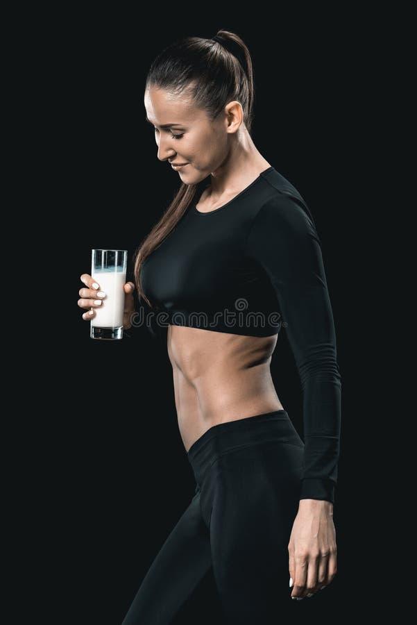 Donna in abiti sportivi che tengono bicchiere di latte e che sorridono, concetto vivente sano immagini stock