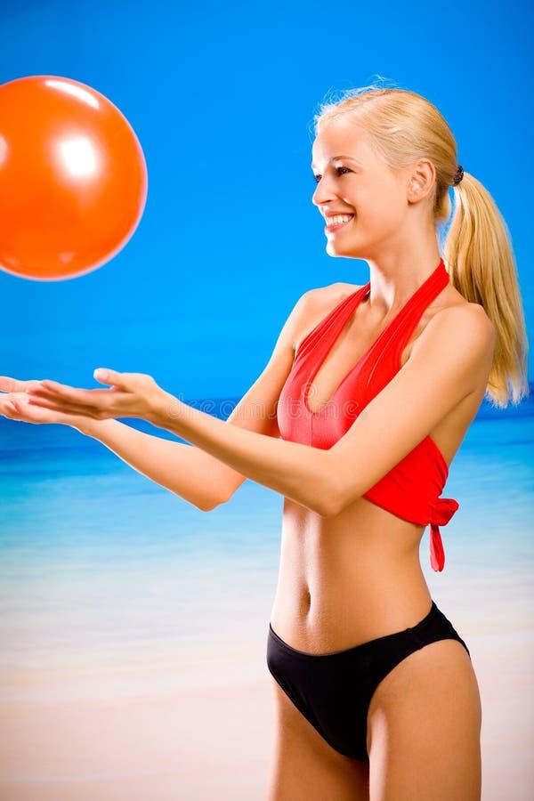 Donna in abiti sportivi sulla spiaggia immagine stock