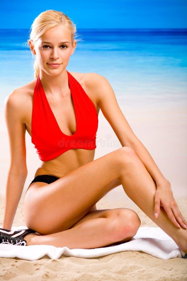 Donna in abiti sportivi sulla spiaggia fotografia stock
