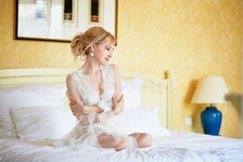 Donna in abito elegante di resto del pizzo che si siede sul letto al primo mattino fotografia stock