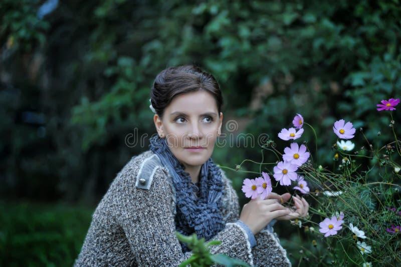 Donna accanto ai fiori immagini stock