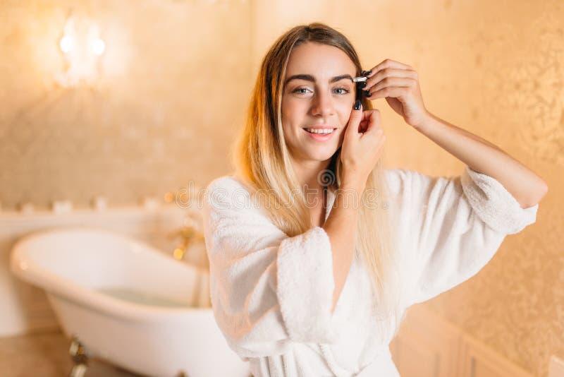 Donna in accappatoio bianco che fa trucco in bagno fotografia stock libera da diritti