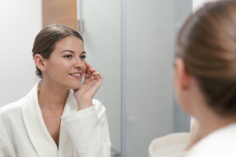Donna in accappatoio che esamina in specchio il bagno fotografia stock