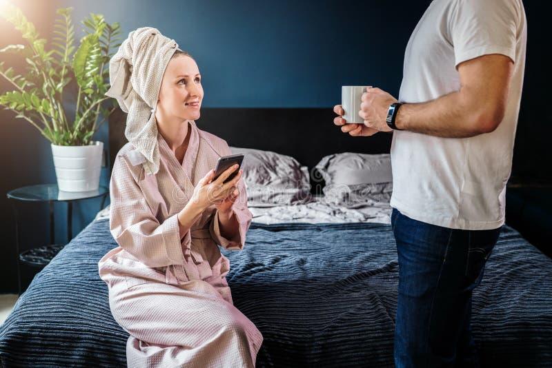 Donna in accappatoio ed asciugamano sulla testa che si siede sul letto, tenendo smartphone, parlante con stare accanto al suo mar fotografia stock libera da diritti