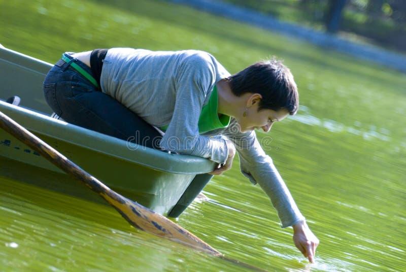 Donna in acqua commovente del rowboat   immagine stock libera da diritti
