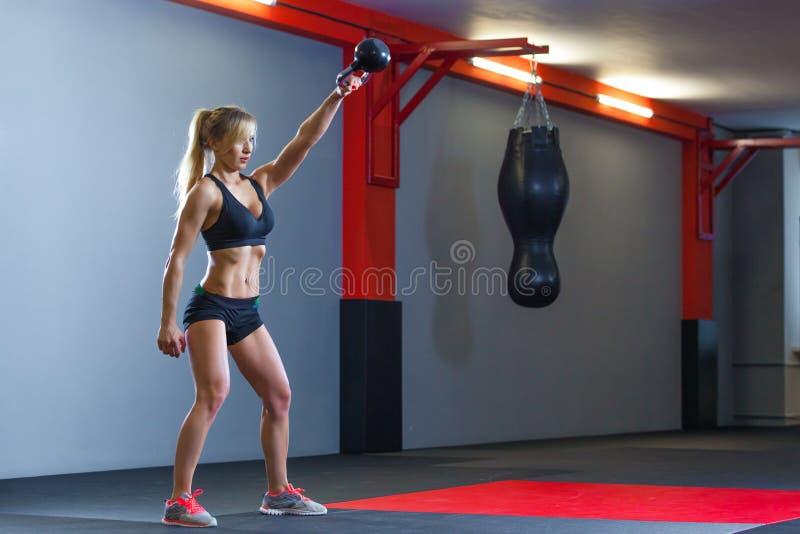 Donna adatta che fa gli edifici occupati con kettlebell nel club di sport Ginnastica immagini stock