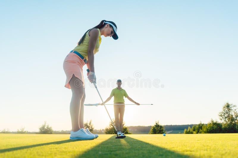 Donna adatta che si esercita colpendo tecnica durante la classe di golf con fotografia stock
