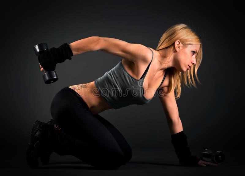 Donna adatta che si esercita con i pesi immagini stock