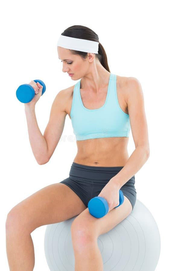 Donna adatta che si esercita con le teste di legno sulla palla di forma fisica fotografia stock libera da diritti