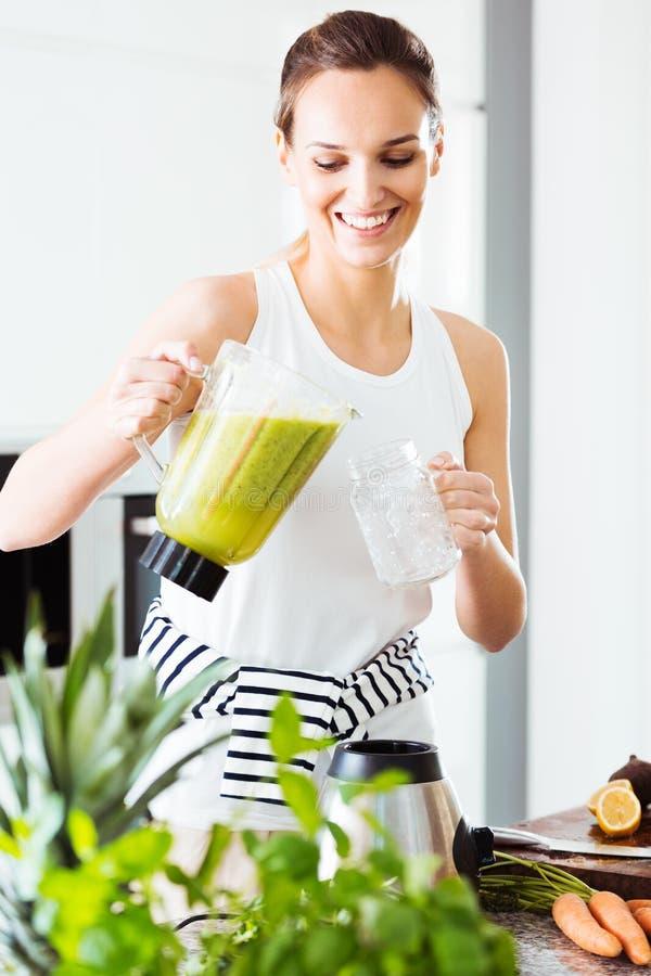 Donna adatta che versa cocktail verde fotografia stock libera da diritti