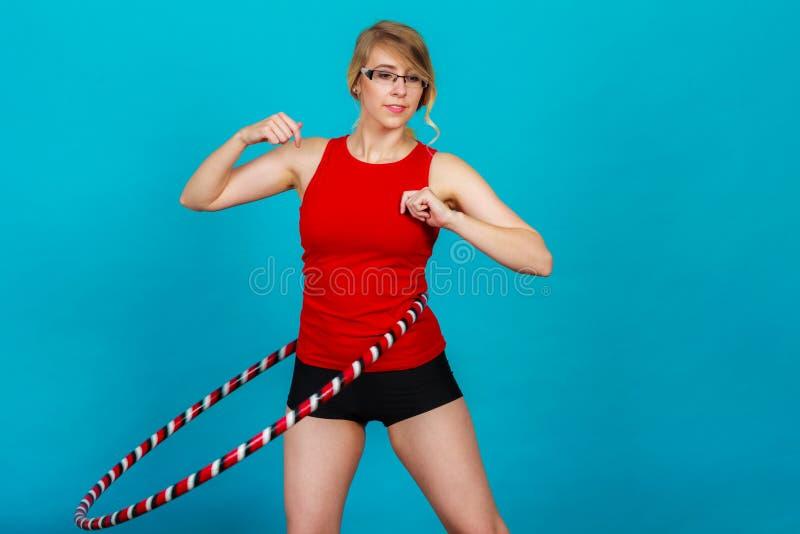 Donna adatta con il hula-hoop che fa esercizio immagini stock