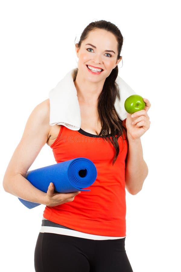 Donna adatta con la stuoia e la mela di yoga immagini stock libere da diritti