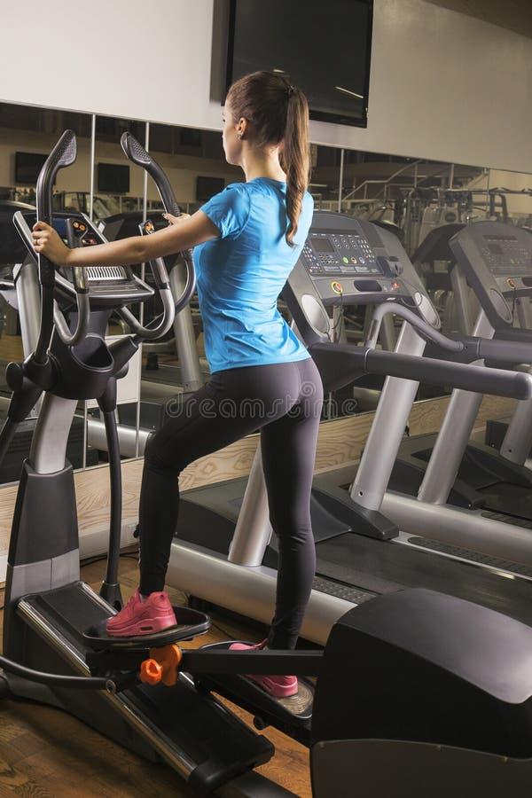 Donna adatta dei giovani che utilizza un istruttore ellittico in un centro di forma fisica, colpo posteriore Ritratto della ragaz fotografie stock