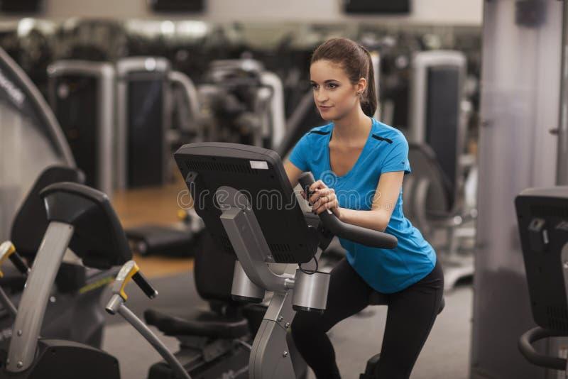 Donna adatta dei giovani che utilizza una bicicletta in un centro di forma fisica, cardio Ritratto della ragazza di forma fisica  fotografia stock