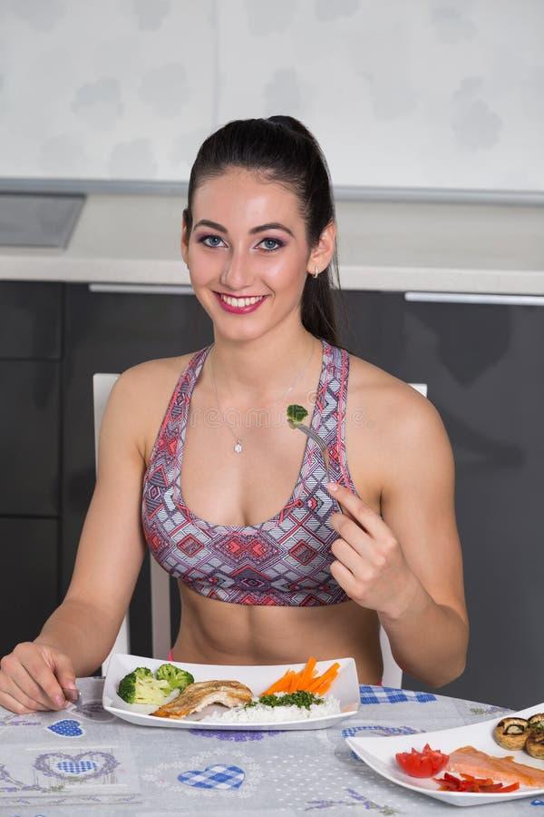 Donna adatta dei giovani nella cucina, mangiante immagini stock libere da diritti