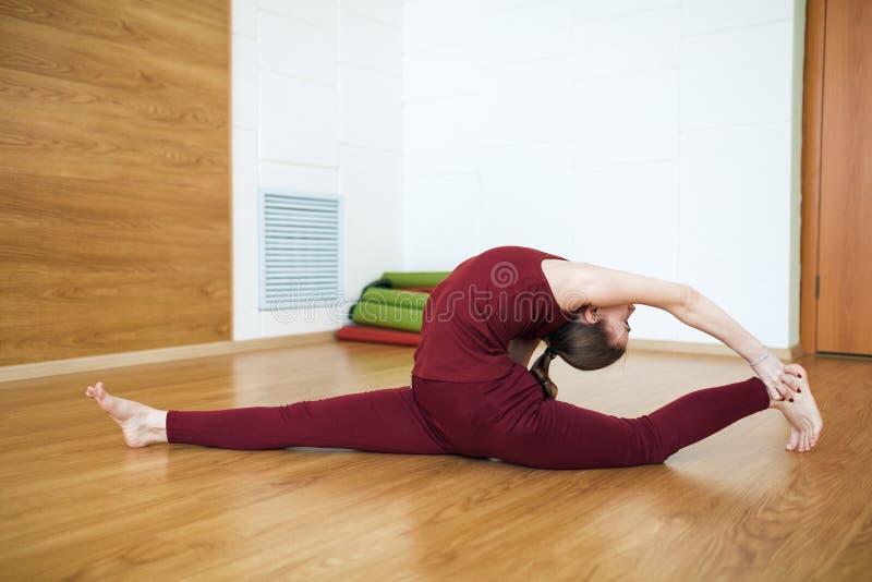 Donna adatta dei giovani in un concetto di pratica di yoga del vestito rosso, allungante nell'esercizio di Dio della scimmia, spa immagini stock libere da diritti