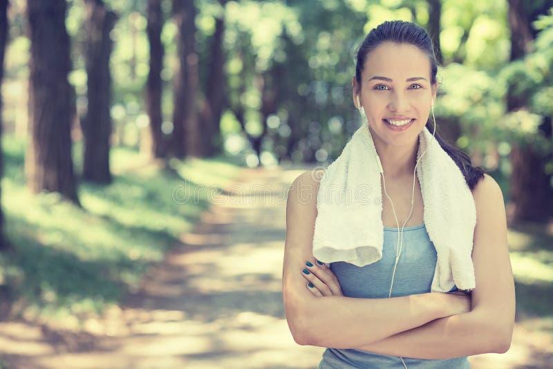 Donna adatta sorridente attraente con l'asciugamano bianco che riposa dopo l'allenamento fotografie stock libere da diritti