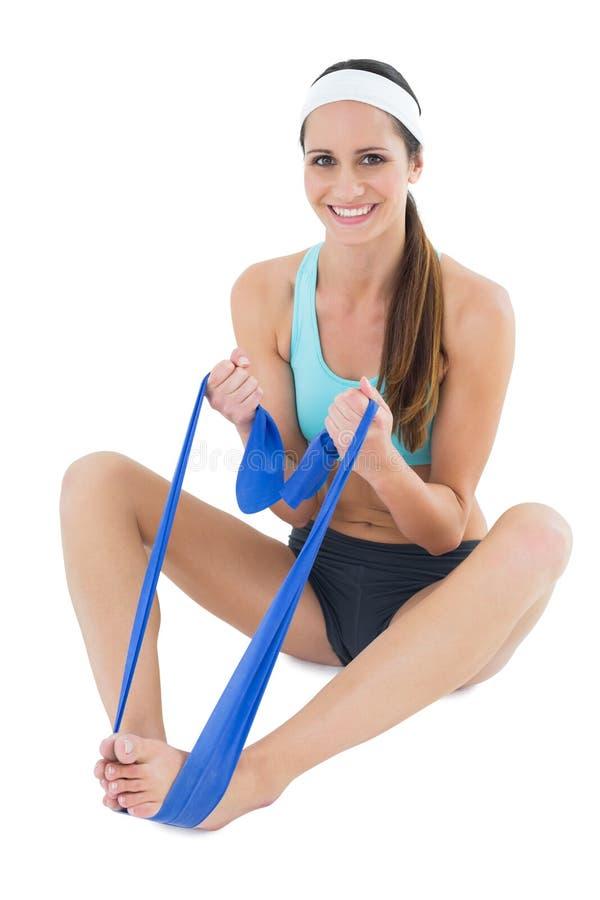 Donna adatta sorridente che si esercita con una cinghia blu di yoga fotografia stock libera da diritti