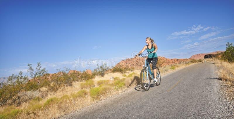 Donna adatta su un giro della bici immagini stock