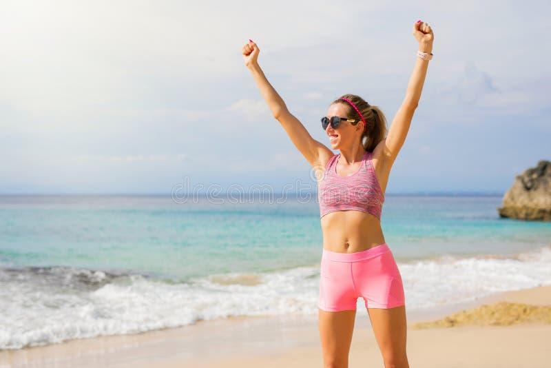 Donna adatta sulla spiaggia che ritiene eccitata fotografie stock libere da diritti