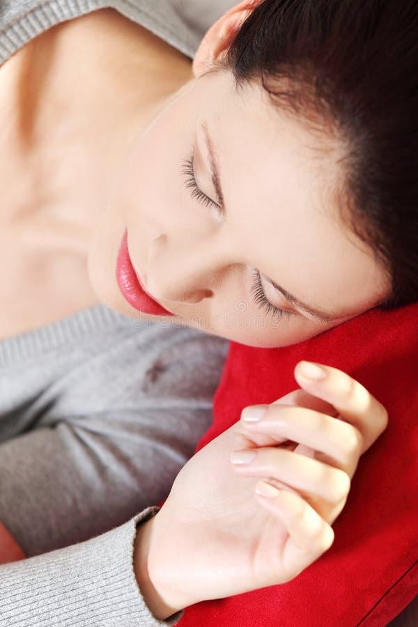 Donna addormentata che si trova su un cuscino rosso. fotografie stock
