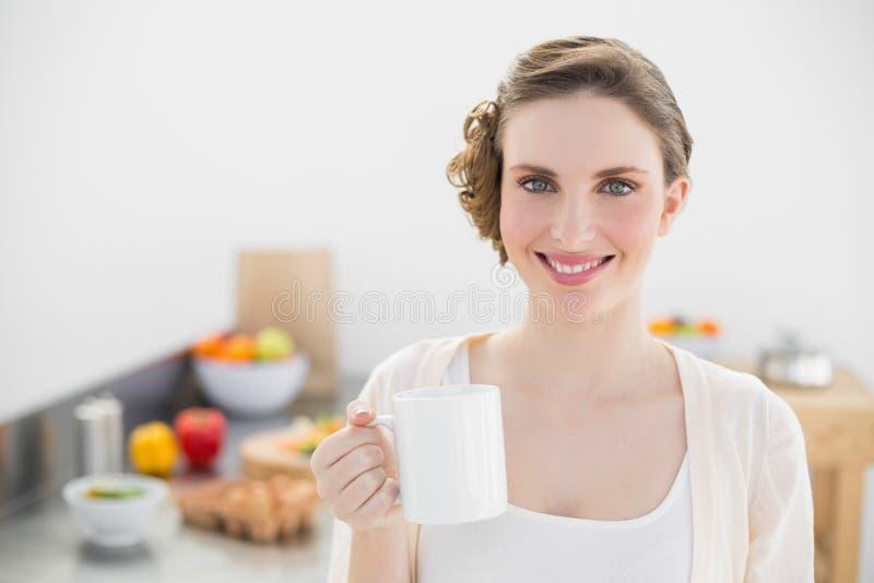 Donna adorabile allegra che sta nella sua cucina che tiene una tazza immagine stock libera da diritti