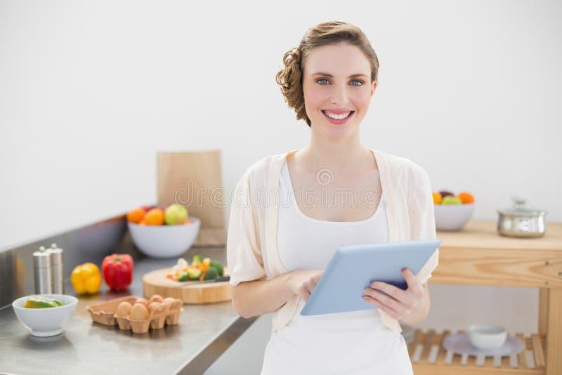 Donna adorabile allegra che tiene la sua compressa che sta nella sua cucina fotografia stock libera da diritti