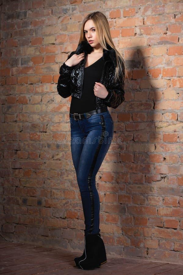 Donna adorabile che posa vicino ad un muro di mattoni fotografia stock libera da diritti