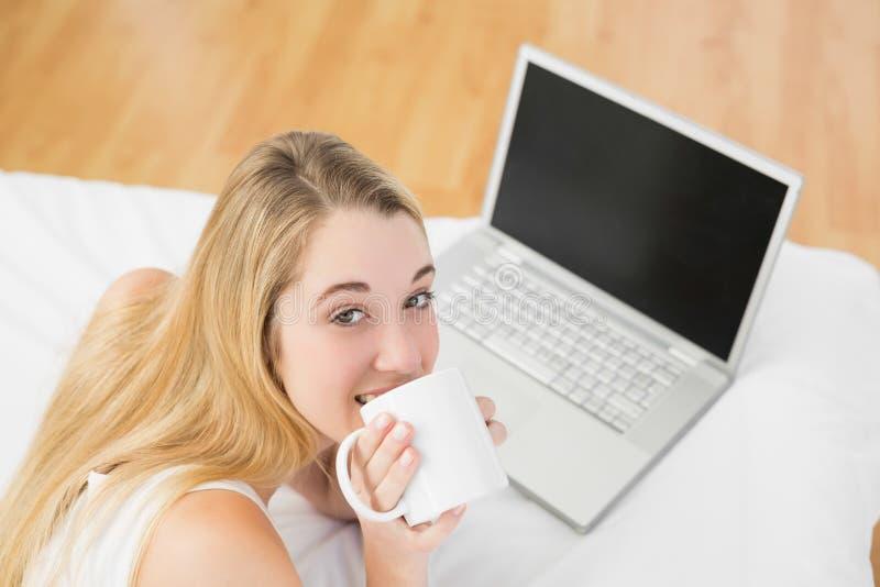 Donna adorabile che si trova sul letto accanto a bere del computer portatile della tazza immagine stock libera da diritti