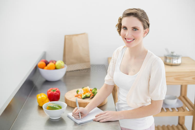 Donna adorabile che sta nella sua cucina che redige una lista di acquisto fotografia stock libera da diritti